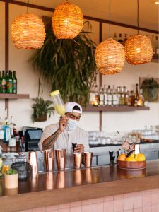 Bartender wearnig backward baseball hat and medical mask prepares a cocktail behind bar